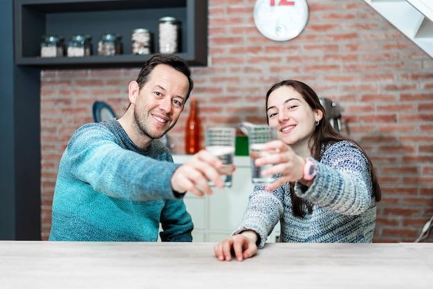 Duas pessoas sorridentes segurando um copo d'água