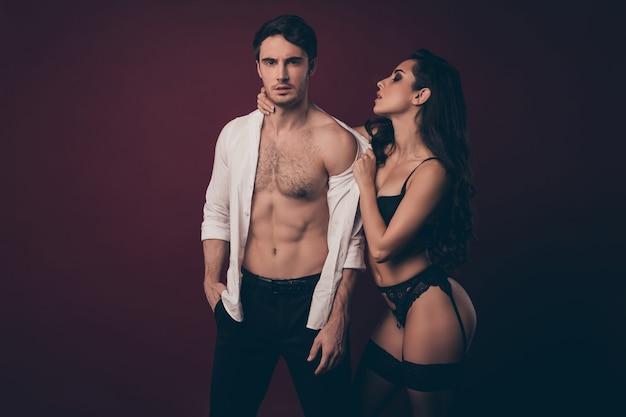 Duas pessoas tentadoras homem mulher posando. mulher despindo homem