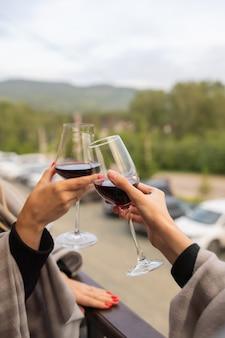 Duas pessoas tilintando com taças de vinho tinto, celebrando o sucesso ou fazendo um brinde no restaurante de vinhos, contra prateleiras com garrafas de vinho, de perto.