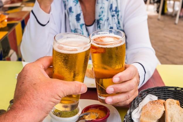 Duas pessoas tomam um copo de cerveja gelada com alguns petiscos. cerveja refrescante e dourada. mesa de bar