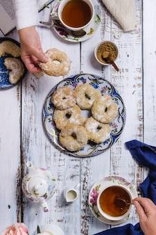 Duas pessoas tomando chá e alguns doces em uma mesa de madeira branca