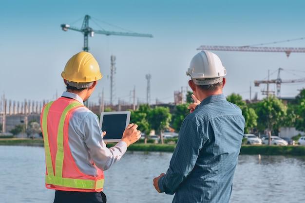 Duas pessoas, trabalhador, engenheiro, conversando sobre um tablet no local de construção de imóveis