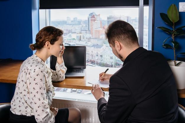 Duas pessoas trabalhando no escritório, assinando contrato