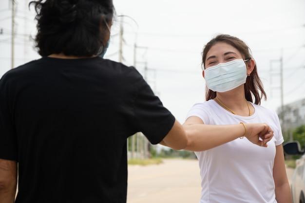 Duas pessoas usam máscara de cotovelo apertando a mão