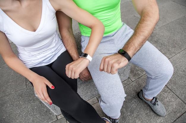 Duas pessoas usando relógio esporte inteligente no treino.