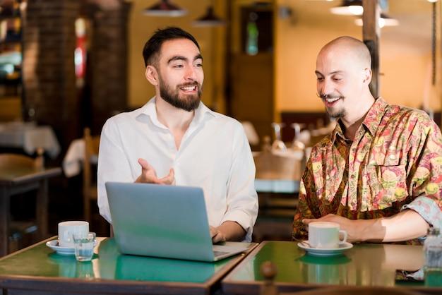 Duas pessoas usando um laptop em uma reunião em uma cafeteria.