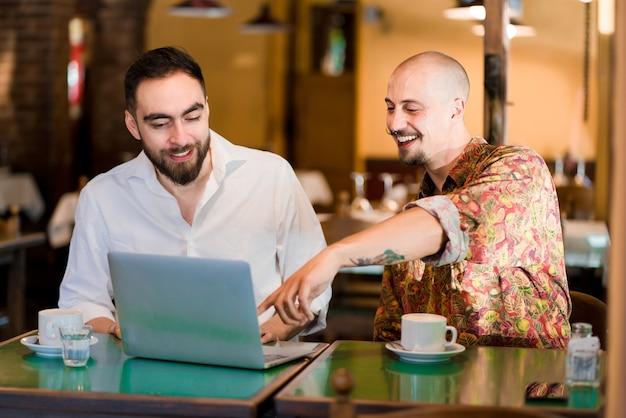 Duas pessoas usando um laptop juntas durante uma reunião em uma cafeteria.