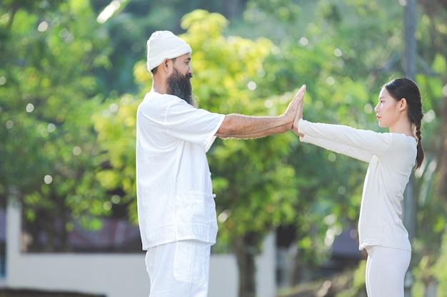 Duas pessoas vestidas de branco fazendo ioga na natureza