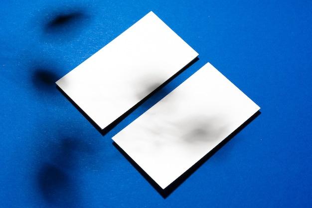 Duas pilhas de cartões de visita em branco sobre fundo azul