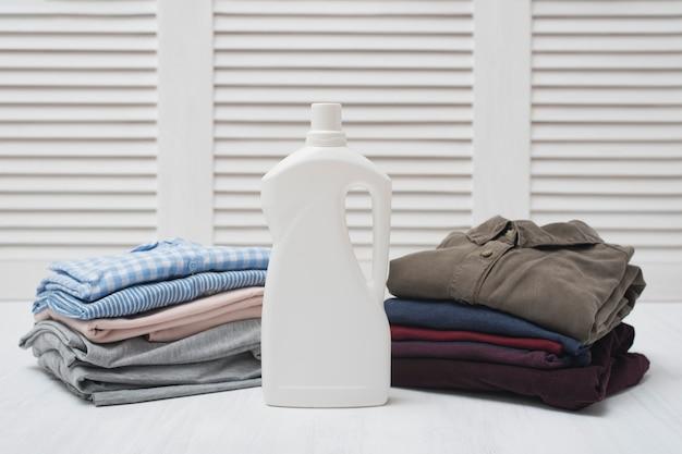Duas pilhas de roupas dobradas e garrafa de detergente. linho escuro e claro
