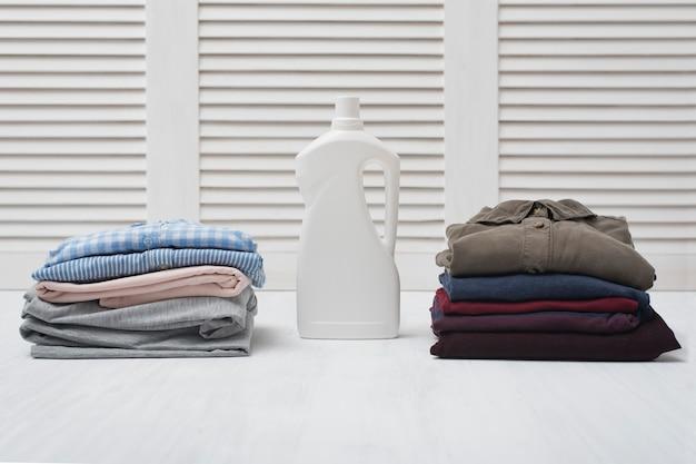Duas pilhas de roupas dobradas e garrafa de detergente