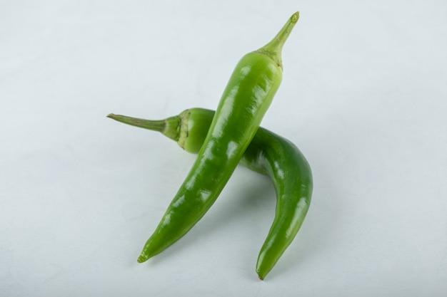 Duas pimentas verdes quentes em fundo branco.