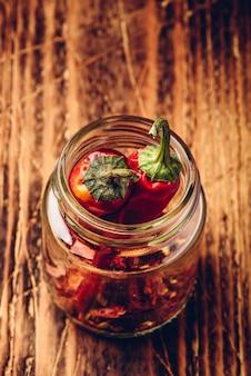 Duas pimentas vermelhas secas em uma jarra com pimentas moídas
