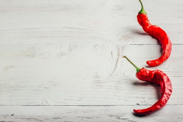 Duas pimentas vermelhas sobre fundo claro de madeira.