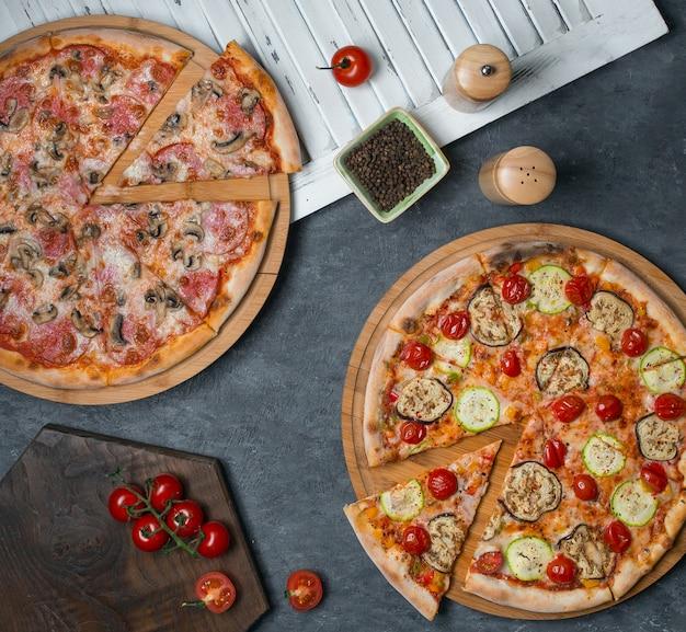 Duas pizzas com ingredientes misturados
