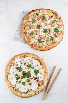 Duas pizzas com recheios diferentes com molho césar, filé de frango, cogumelos mel, cogumelos, tomate e queijo mussarela em fundo claro. vista superior com um espaço de cópia para o texto.