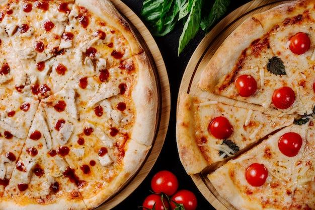Duas pizzas diferentes com tomate cereja e calabresa.