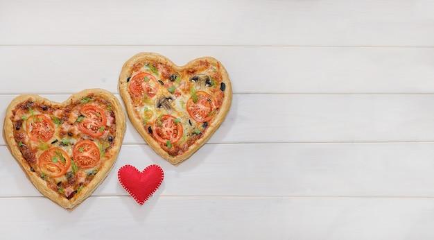 Duas pizzas em forma de coração em uma mesa de madeira branca com espaço de cópia com um coração vermelho. dia dos namorados, amor.