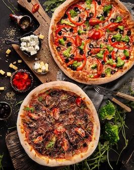 Duas pizzas no armário de madeira e alguns ingredientes e especiarias ao redor