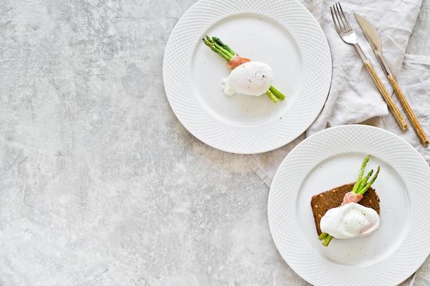 Duas placas com um ovo cozido no aspargo roasted envolvido no bacon.