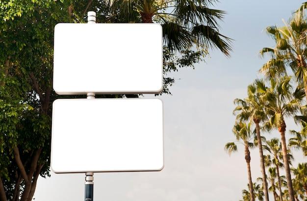 Duas placas de publicidade em branco com árvores e céu azul ao fundo