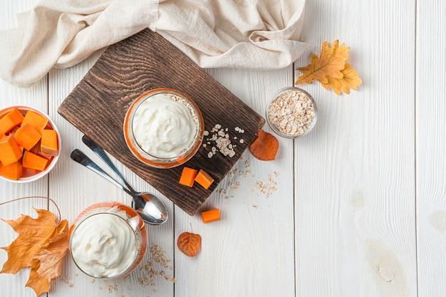 Duas porções de parfait de abóbora com cereais em um fundo claro sobremesa saudável de outono