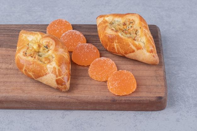 Duas porções de pide e marmeladas em uma placa de madeira na mesa de mármore.