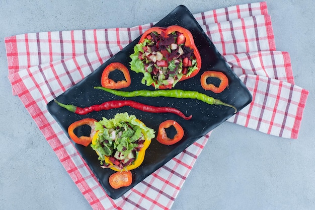 Duas porções de salada em uma travessa decorada com fatias de pimentão e pimenta em superfície de mármore