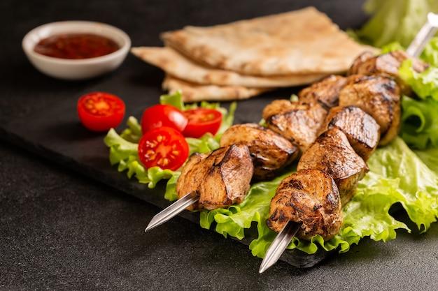Duas porções de shish kebab em um prato de pedra com salada.