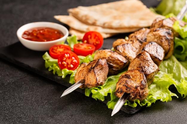 Duas porções de shish kebab num prato de pedra com salada.