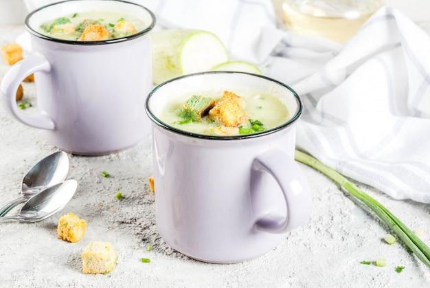 Duas porções de sopa cremosa de abobrinha caseira com migalhas de pão em canecas