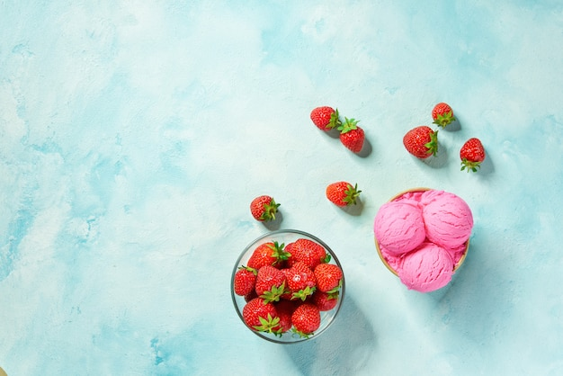Duas porções de sorvete de morango em copo de papel com fundo de cores hortelã, vista superior