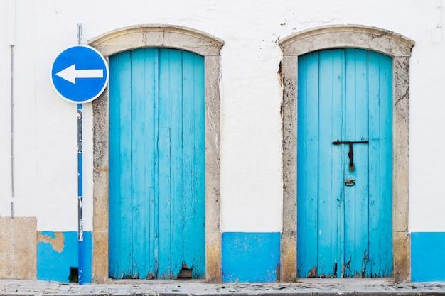 Duas portas azuis e sinal de trânsito azul