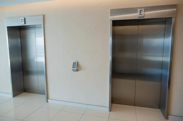 Duas portas de elevador no saguão do prédio de escritórios