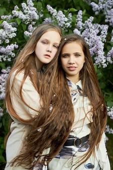 Duas poses de garota em um arbusto de lilases na primavera. retrato romântico de uma garota em flores sob a luz do sol