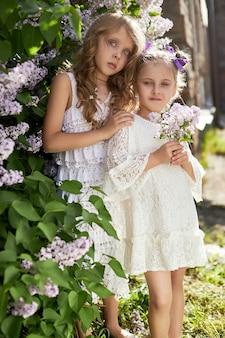 Duas poses de garota em um arbusto de lilases na primavera. retrato romântico de uma menina em flores sob a luz do sol