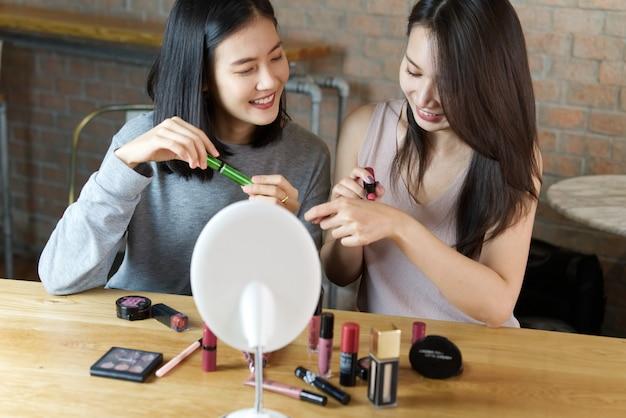 Duas raparigas que fazem um vídeo para seu blog em cosméticos.