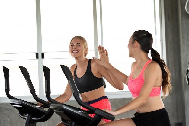 Duas raparigas são sorriso feliz e dando cinco com a bicicleta de exercício no ginásio.