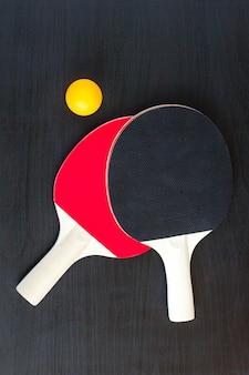 Duas raquetes de tênis de mesa ou ping pong e bola em um fundo preto