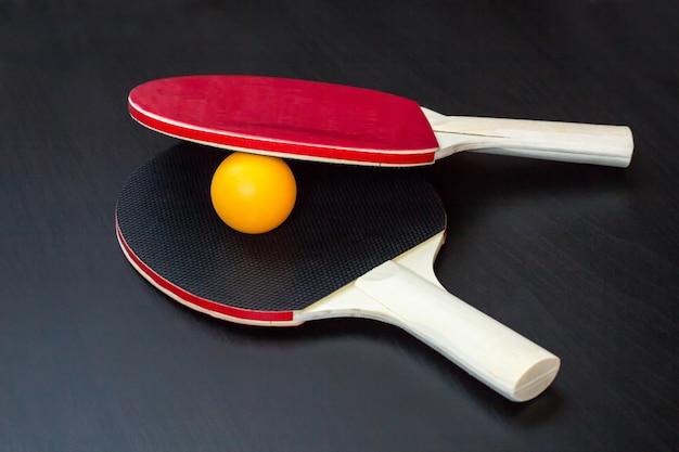 Duas raquetes de tênis de mesa ou ping pong e bola em uma mesa preta