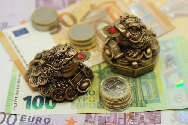 Duas rãs chinesas do feng shui sentadas nas notas de euro