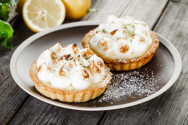 Duas saborosas tortinhas de limão e merengue com hortelã no prato em pé na velha mesa de madeira