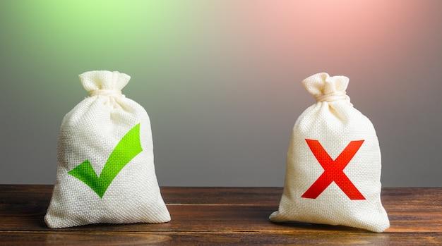 Duas sacolas com uma marca de seleção verde e uma cruz vermelha planejamento de riscos vantagens e desvantagens