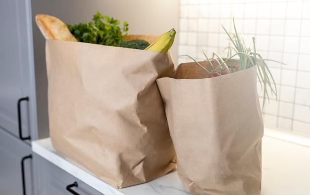 Duas sacolas de papel de supermercado na bancada da cozinha com produtos frescos