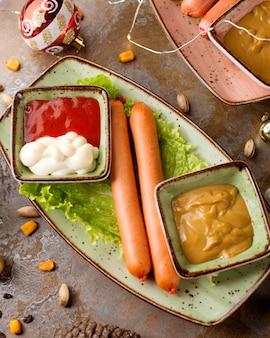 Duas salsichas em cima da mesa com ketchup e mostarda