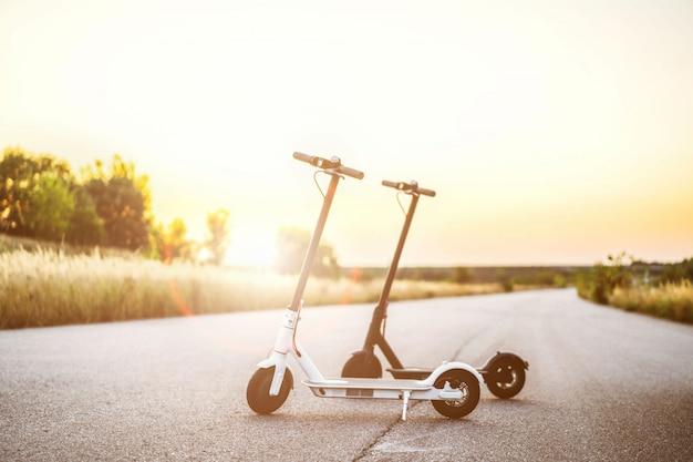 Duas scooters elétricas, preto e brancas, ficam no meio da estrada na hora do pôr do sol na zona rural. tecnologias de conteúdo. novo movimento
