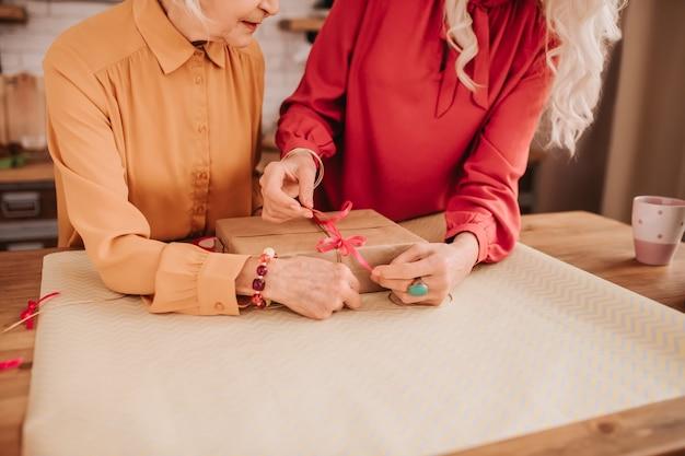 Duas senhoras bonitas de idade avançada com roupas brilhantes em pé perto da mesa