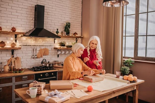 Duas senhoras idosas bonitas com roupas brilhantes passando um tempo juntas