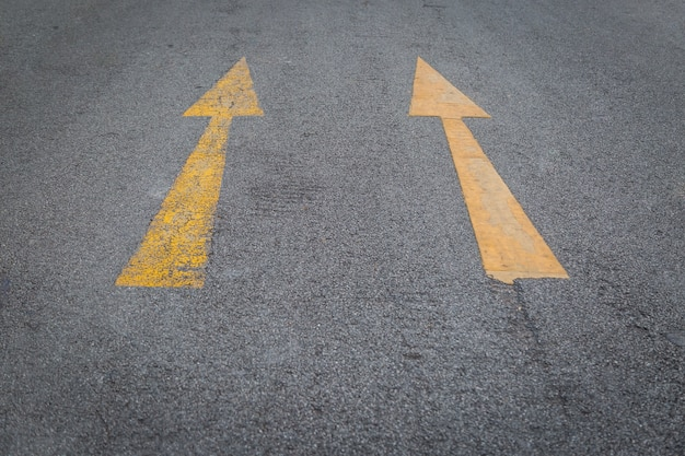 Duas setas amarelas velhas e novas direção fundo de estrada de asfalto