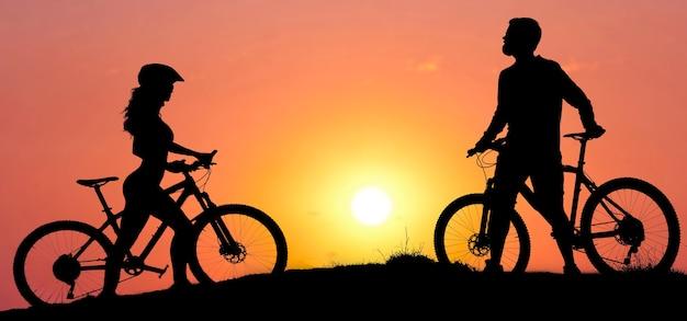 Duas silhuetas de ciclistas em um fundo por do sol. atleta e uma garota em modernas mountain bikes